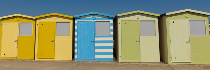 Beach huts in a row with green blue and yellow colours and blue sky panoramic view