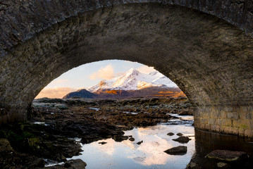 snow covered mountains framed by stone bridge arch at sunrise
