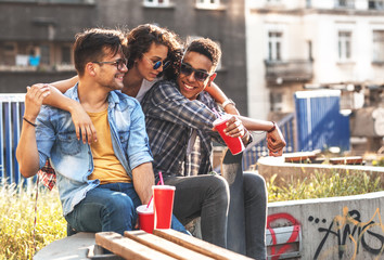 Group of friends hangout  at the street.They embrace each other and drinking cold juice.Fast food.