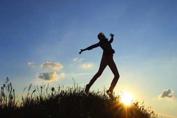 Silhouettes Of A Happy Young Teenage Girl Jumping Over Sunset Background. An Attractive Young Girl Jumping In The Air At The Sunset.