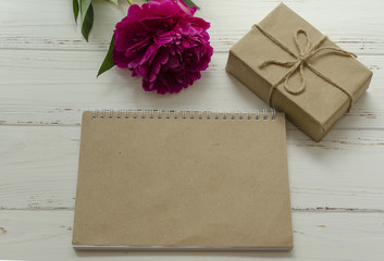 peony, gift box, empty notepad craft paper sheet on wooden background