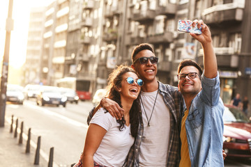Group of friends hangout  at the city street.They embrace each other and doing selfie.