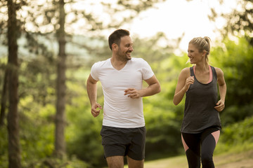 Couple jogging outdoors in nature Wall mural