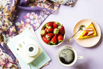 Spring breakfast with cheesecake, coffee and strawberries next to a stylish white camera and scarf with floral print on a purple background. Top view, flat lay