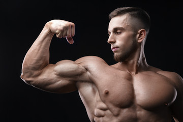 Handsome power athletic man bodybuilder demonstrates his biceps.
