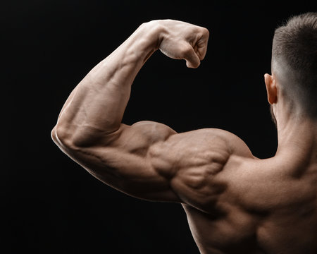 Bodybuilder in good shape against a dark background