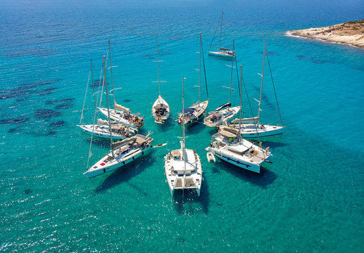 Sailing boats in a star formation in turquoise tropical bay. View from above.