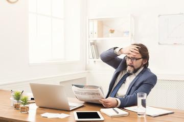 Businessman reading bad breaking news in newspaper