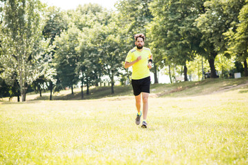 Young adult male runner jogging in nature