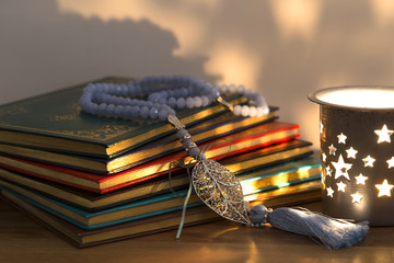 Koran and rosary on the white background with  candle for Islamic concept. Holy book Quran for Muslims for Ramadan and three months.
