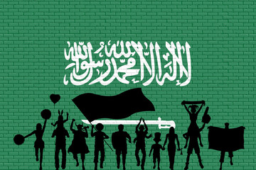 Arab supporter silhouette in front of brick wall with Saudi Arabia flag