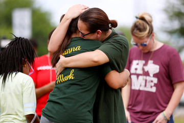 Mourners embrace at a makeshift memorial left in memory of the victims killed in a shooting at Santa Fe High School in Santa Fe