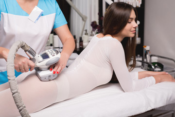 Female having procedure of massage on legs in apparatus cosmetology clinic. Woman in special white suit getting anti cellulite massage in a spa salon. LPG treatment.