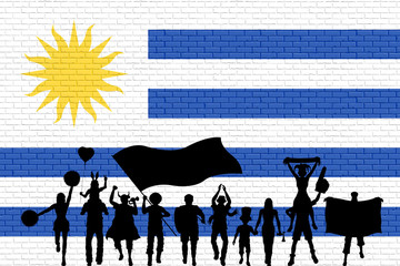Uruguayan supporter silhouette in front of brick wall with Uruguay flag