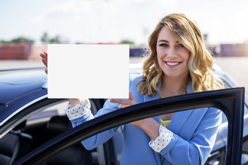 Woman standing by car holding a white blank poster.