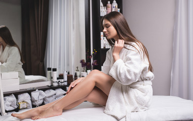 Beautiful young woman in a modern beauty salon showing her perfect slim legs