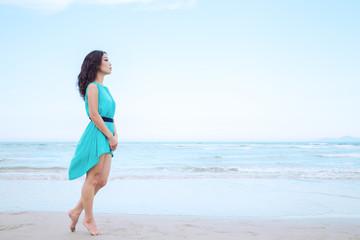 Young beautiful asian woman is walking along the beach