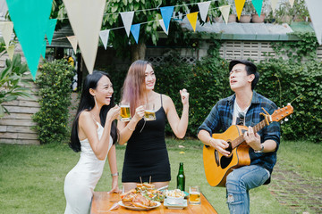 Group of friends having party in home garden.Happy young mates enjoying party playing guitar, singing and drinking beer eating food in garden.
