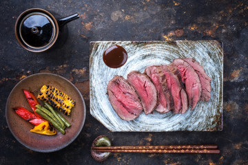 Japanese barbecue wagyu aged fillet steak with vegetable slices as top view on a plate