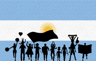 Argentinian supporter silhouette in front of brick wall with Argentina flag