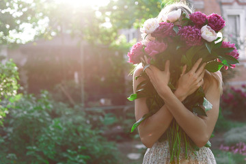 girl in the garden with a big bouquet of peonies in hands at sunset Fototapete
