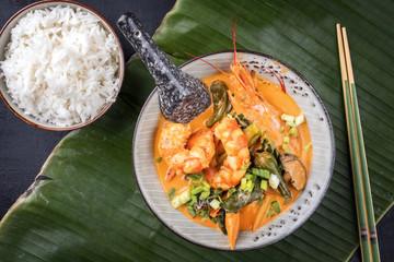 Traditionelles Thai Kaeng Phet Red Curry mit Garnelen und Reis als Draufsicht in einer Schale auf einem Bananenblatt