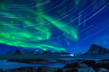Northern Lights, Aurora Borealis shining green in night starry sky with star tracks at winter Lofoten Islands, Norway