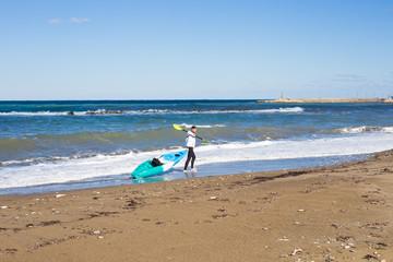 Man carrying his kayak along the shore.