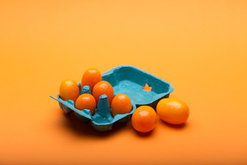 Cumquats in a blue box on orange background