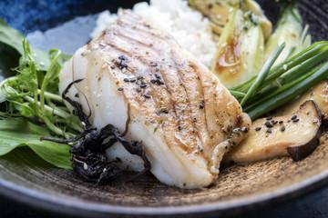 Modern japanisch gebratenes Kabeljau Fisch Filet mit Pak Choi und Reis als closeup in einem Teller