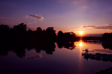 Fisherman silhouette on sunset background. Friends fishers enjoy fishing on river dock.