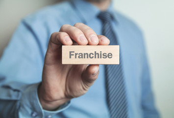 Businessman showing Franchise word in wooden block.