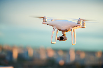 drone flying over evening city with digital camera