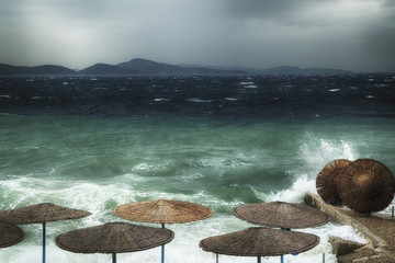 strong storm, waves and wind at sea, waves washed away beach umbrellas