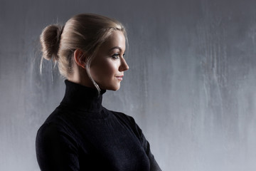 Portrait of beautiful blonde woman. Calm and self-confidence. Beautiful adult girl in black turtleneck, gray background