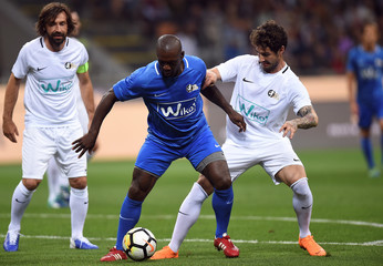 Former player Clarence Seedorf in action with Alexandre Pato during Andrea Pirlo's farewell soccer match at the San Siro stadium in Milan