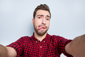 Don't be shy! Close up portrait of excited sincere openhearted emancipated handsome guy fooling around on camera and taking selfie, isolated on gray background