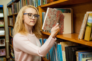 A girl with glasses chooses a book in the library