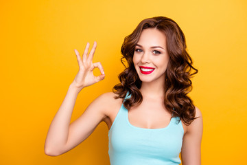 Advertisement concept. Portrait of trendy charming girl with modern hairdo red lipstick pomade showing ok symbol with fingers looking at camera isolated on yellow background