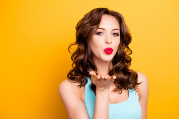 Portrait of pretty seductive woman with modern hairdo sending blowing air kiss with palm pout lips to the camera isolated on yellow background