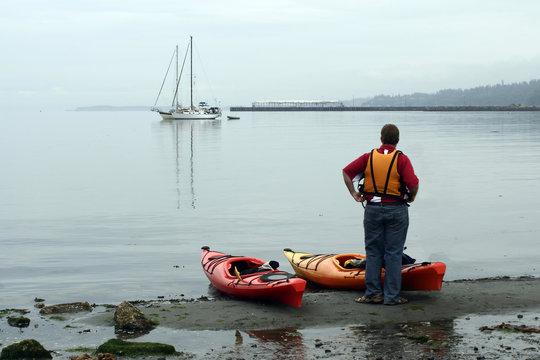 Unidentified man wearing orange life preserver, with kayaks at shoreline of Port Angeles, Washington State