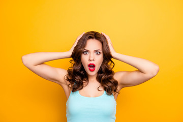 WTF! Portrait of irritated impressed woman holding two hands on head keeping wide open mouth looking at camera isolated on yellow background