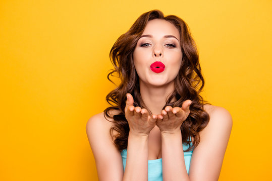 Portrait of lovely sweet girl with modern hairdo blowing air kiss with pout lips two palms at camera isolated on yellow background demonstrate feelings to her boyfriend