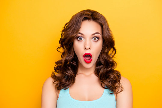 WTF! OMG! Portrait of shocked astonished girl with modern hairdo having wide open mouth eyes looking at camera isolated on yellow background