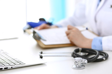 Closeup of stethoscope. Female doctor fills up medical form while sitting at the desk in hospital. Healthcare, workplace and cardiology in medicine concept