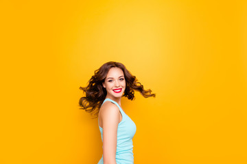 Portrait of excited playful girl turning with flying hair looking at camera enjoying summer time isolated on yellow background