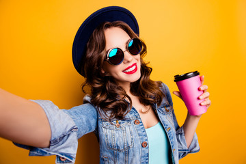 Self portrait of cheerful tourist with beaming smile toothy positive blogger shooting selfie on front camera with hand holding mug with tea hot beverage having video-call, travel tourism concept