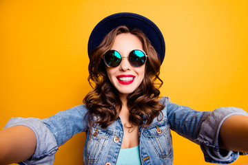 Self portrait of positive toothy girl shooting selfie on front camera with two hands having red lipstick beaming smile modern hairdo isolated on yellow background, photography concept