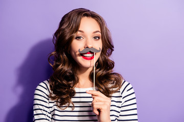 Portrait of crazy trendy chic with beaming smile having carton paper black cutout mustache on stick looking at camera isolated on violet background