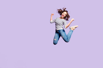 Portrait of successful crazy girl celebrating victory jumping in the air with raised fists yelling isolated on violet background, full of energy people in action concept Wall mural